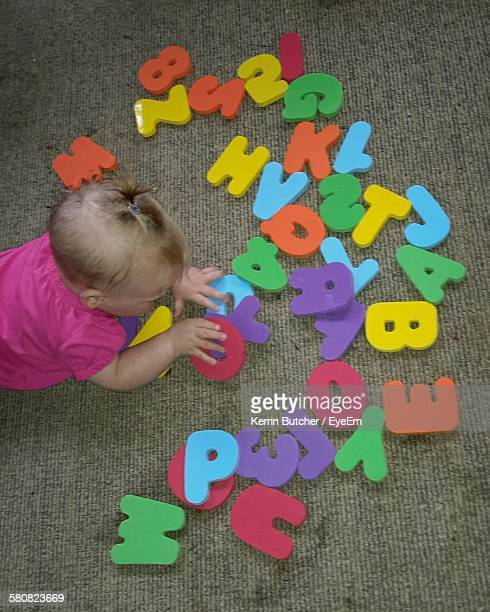 High Angle View Of Toddler Playing With Alphabets On Floor