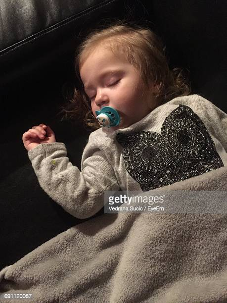 High Angle View Of Toddler Sleeping With Pacifier On Bed
