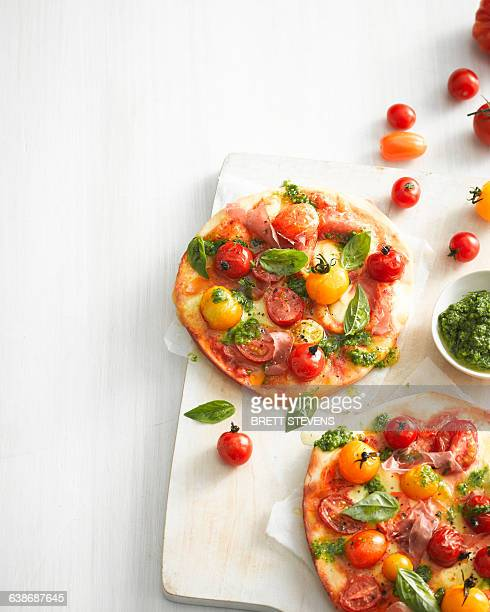 High angle view of tomato, basil and prosciutto pizzas on cutting board