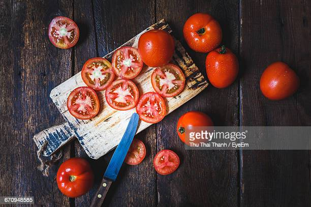 High Angle View Of Tomato Slices With Knife On Cutting Board On Table