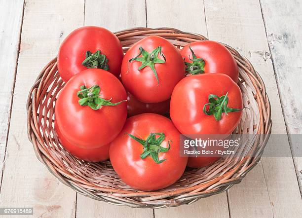 high angle view of tomatoes in wicker basket on table - groupe moyen d'objets photos et images de collection