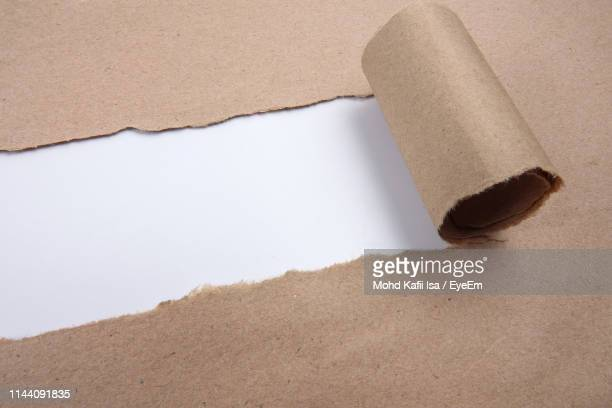 high angle view of torn brown paper on white background - brown paper stock pictures, royalty-free photos & images