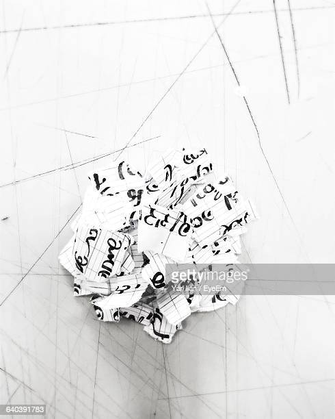 High Angle View Of Torn Paper Pieces On Table
