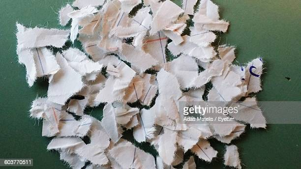 High Angle View Of Torn Papers On Table