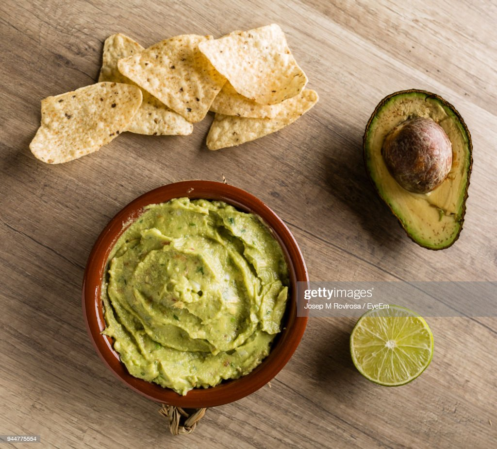 High Angle View Of Tortilla Chips With Avocado On Table : Stock Photo