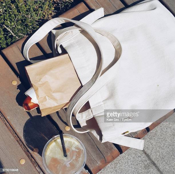 high angle view of tote bag by drink on table - トートバッグ ストックフォトと画像