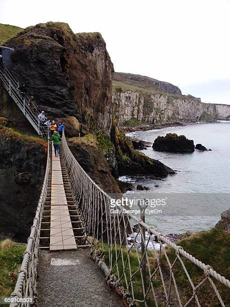 High Angle View Of Tourists On Carrick-A-Rede Rope Bridge In Northern Ireland