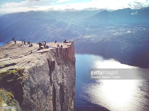 High Angle View Of Tourists On Preikestolen Cliff By River