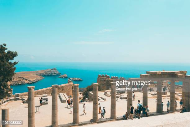 high angle view of tourists visiting archeological site against blue sky during sunny day - lindos stock photos and pictures