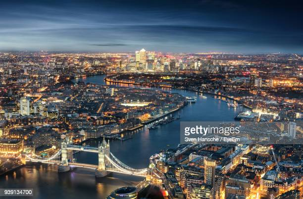 high angle view of tower bridge over thames river in illuminated city at night - isle of dogs london stock pictures, royalty-free photos & images