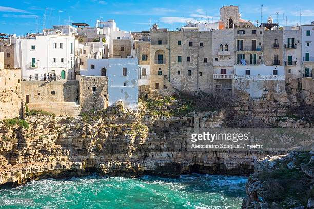 high angle view of town against sky - polignano a mare stock photos and pictures