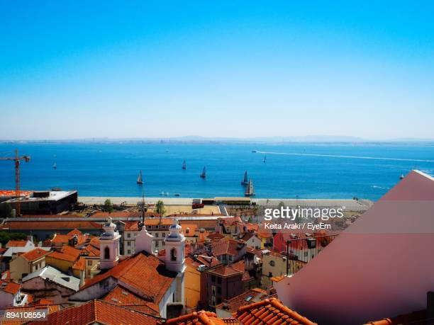 High Angle View Of Town By Sea Against Clear Blue Sky