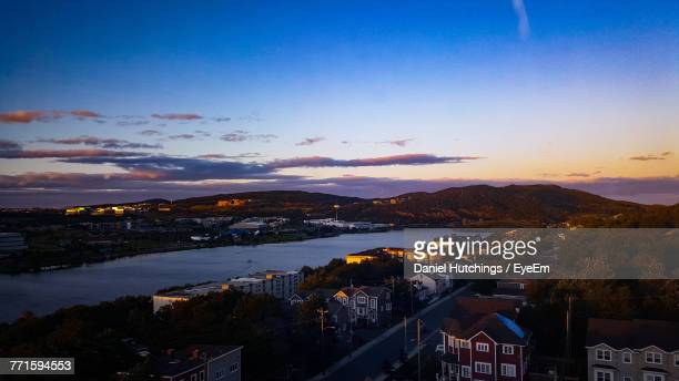 high angle view of town by sea against sky during sunset - st. john's newfoundland stock photos and pictures