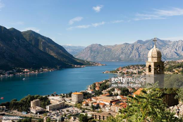 high angle view of town by sea and mountains against sky - montenegro imagens e fotografias de stock