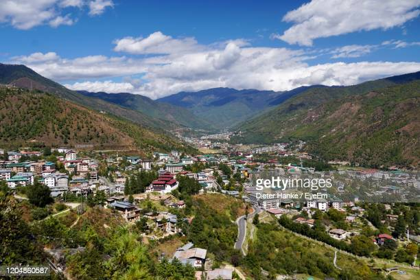 high angle view of townscape and mountains against sky - thimphu stock pictures, royalty-free photos & images