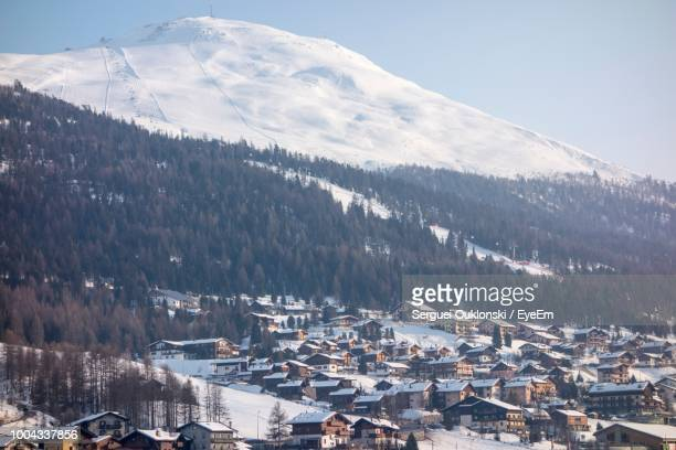High Angle View Of Townscape And Snowcapped Mountains Against Sky