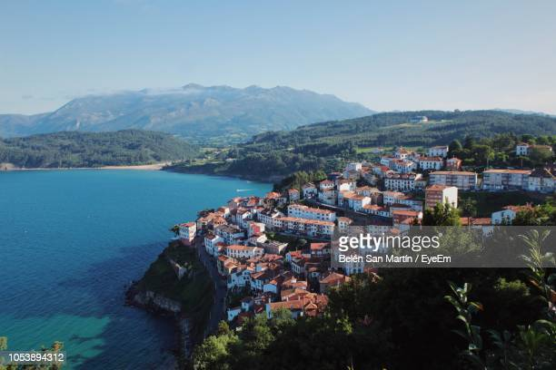 high angle view of townscape by mountain against sky - asturien stock-fotos und bilder