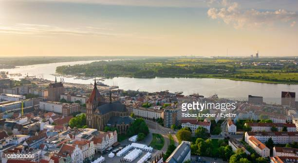 high angle view of townscape by river against sky - rostock stock pictures, royalty-free photos & images