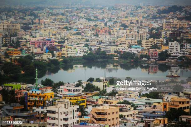 high angle view of townscape by river - hyderabad indien stock-fotos und bilder
