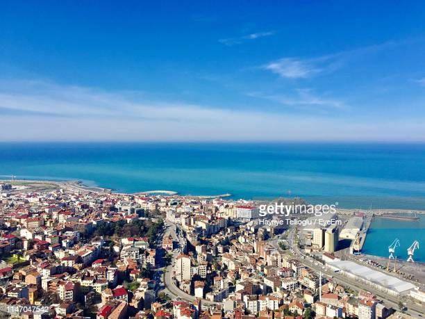 high angle view of townscape by sea against blue sky - trabzon stock photos and pictures
