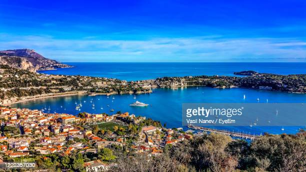 high angle view of townscape by sea against blue sky - saint jean cap ferrat stock pictures, royalty-free photos & images