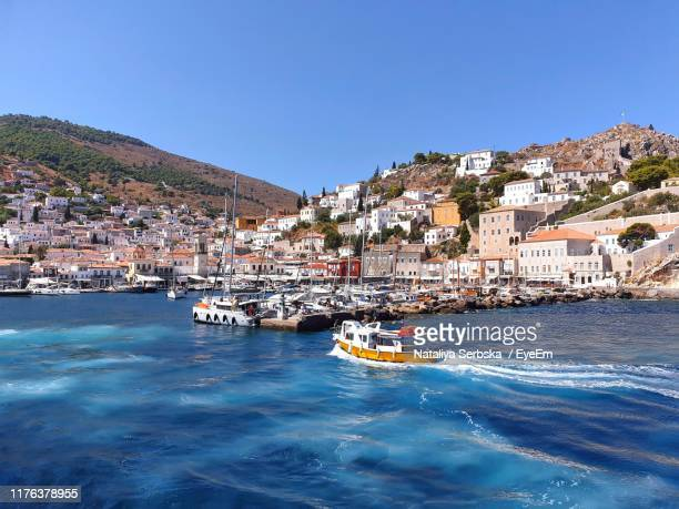 high angle view of townscape by sea against clear blue sky - hydra greece photos stock pictures, royalty-free photos & images