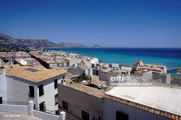 high angle view of townscape by sea against clear blue sky - altea photos et images de collection
