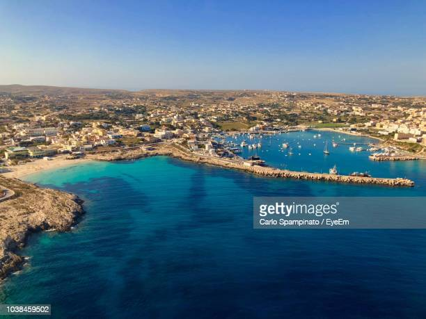 high angle view of townscape by sea against clear sky - lampedusa stock pictures, royalty-free photos & images