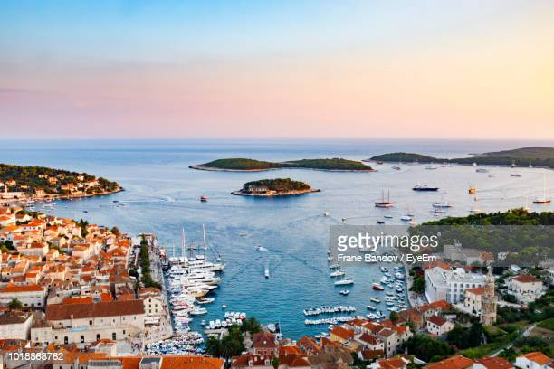 high angle view of townscape by sea against sky during sunset - hvar stock photos and pictures