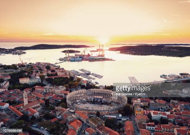 high angle view of townscape by sea against sky during sunset - イストリア半島 プーラ ストックフォトと画像