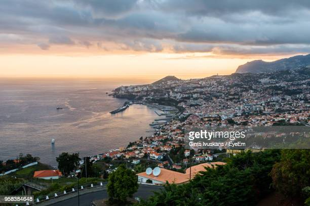 high angle view of townscape by sea against sky during sunset - funchal stock pictures, royalty-free photos & images