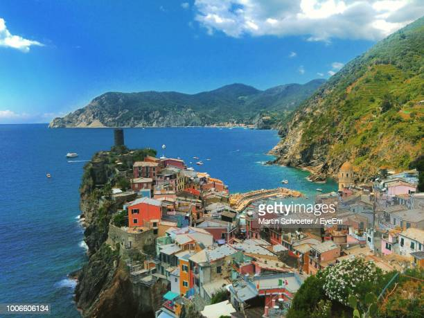 high angle view of townscape by sea against sky - liguria stock photos and pictures