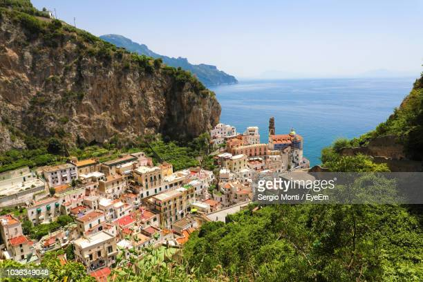 high angle view of townscape by sea against sky - amalfi coast stock photos and pictures