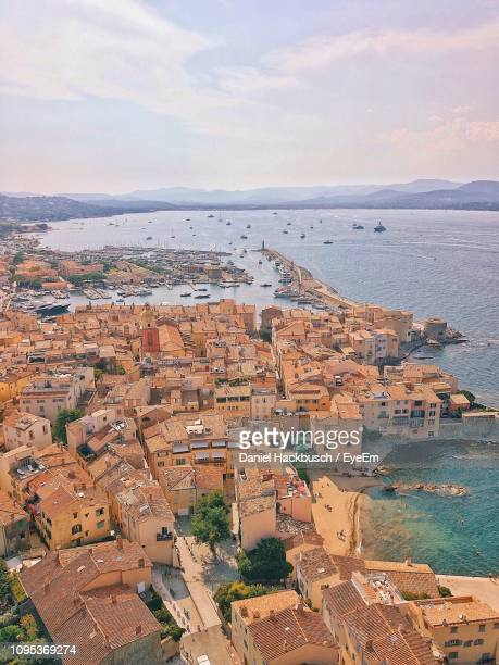 high angle view of townscape by sea against sky - st tropez stock pictures, royalty-free photos & images