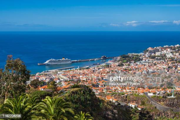 high angle view of townscape by sea against sky - funchal stock pictures, royalty-free photos & images