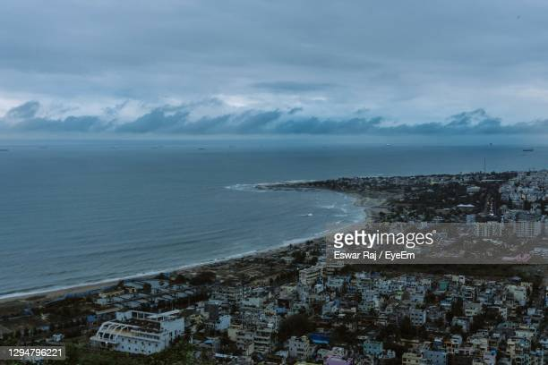 high angle view of townscape by sea against sky - ヴィシャカパトナム ストックフォトと画像