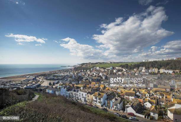 high angle view of townscape by sea against sky - hastings stock photos and pictures