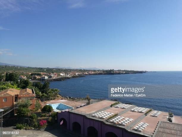 high angle view of townscape by sea against sky - acireale stock-fotos und bilder