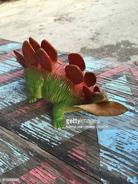 High Angle View Of Toy Dinosaur On Wooden Table