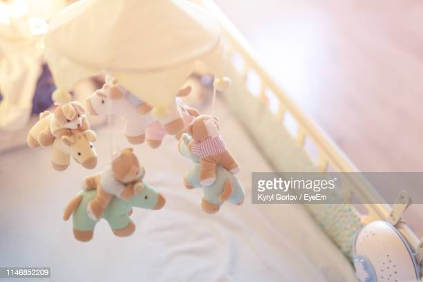 high angle view of toys hanging in crib at home - crib stock pictures, royalty-free photos & images