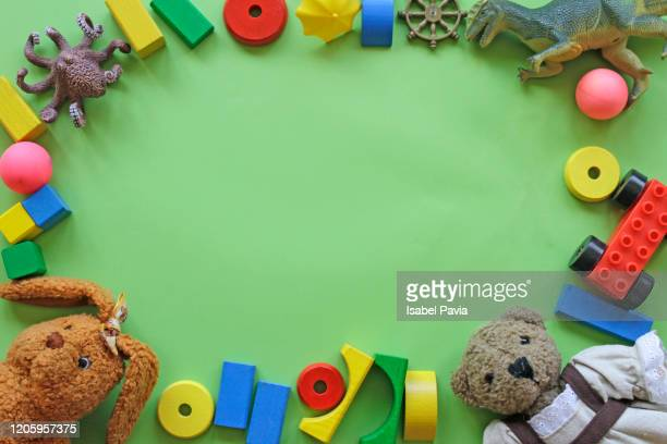 high angle view of toys over green background - niñez fotografías e imágenes de stock