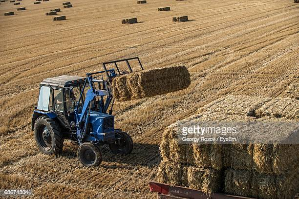 High Angle View Of Tractor With Hay Bales On Field