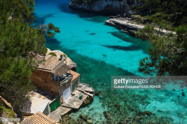 High angle view of traditional boathouse and turquoise sea, Majorca, Spain