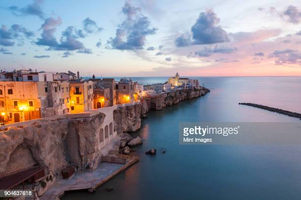 High angle view of traditional houses build on a cliff on the Mediterranean Sea at sunset.