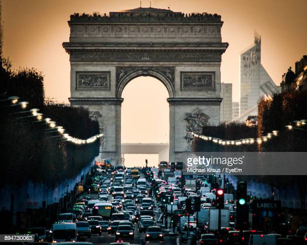 high angle view of traffic at city gate during sunset - arc de triomphe paris stock photos and pictures