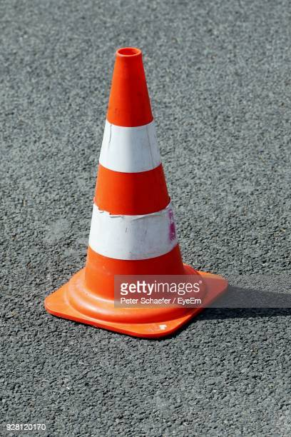 high angle view of traffic cone on street during sunny day - cone shape stock photos and pictures