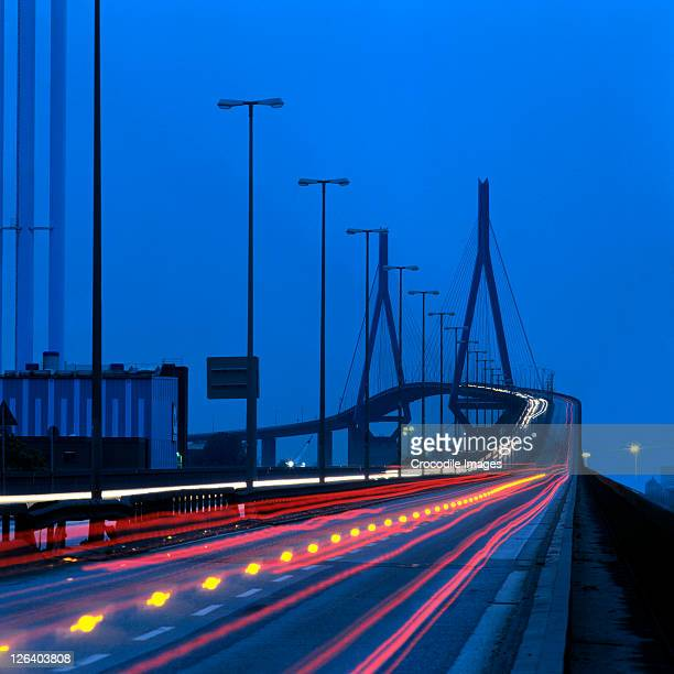 high angle view of traffic in motion at dusk, germany - köhlbrandbrücke stock photos and pictures