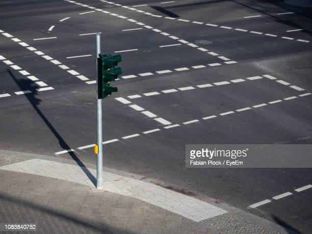 high angle view of traffic light on empty road intersection - freie straße stock-fotos und bilder