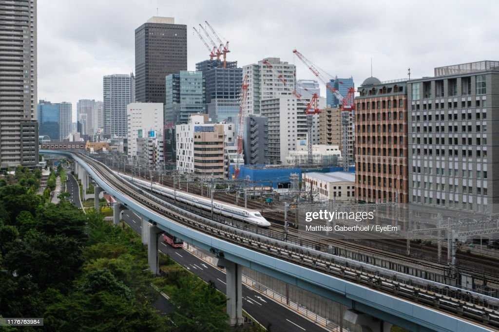 High Angle View Of Train And Railroad Tracks Amidst Buildings In City : Stock-Foto