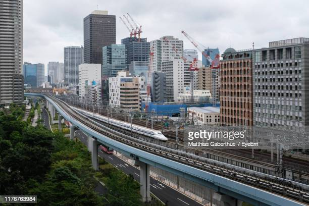 high angle view of train and railroad tracks amidst buildings in city - matthias gaberthüel stock-fotos und bilder
